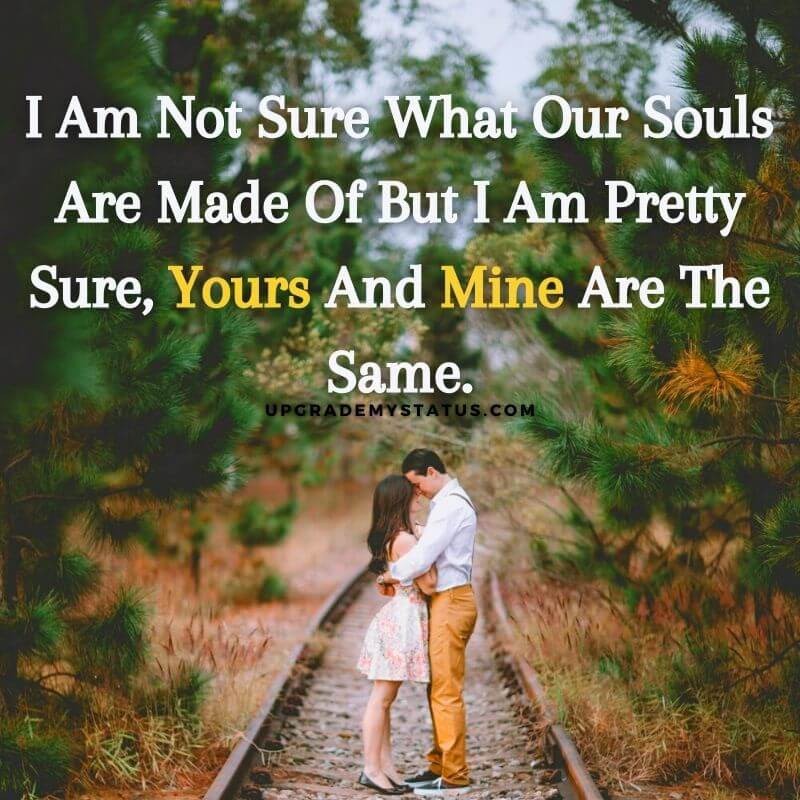 a couple is hugging on a rail road passing through trees over it love status quote is written